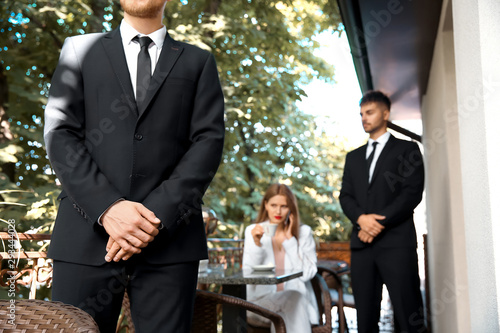 Fotografia, Obraz Young businesswoman with bodyguards in cafe