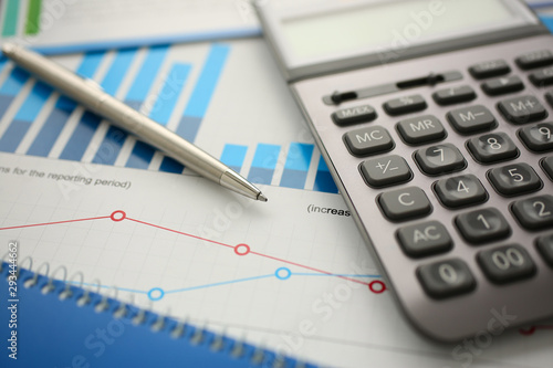 Canvastavla Silver calculator and financial statistics on clipboard pad at office table closeup