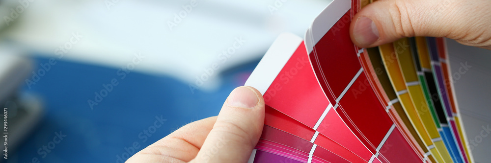 Fototapeta Employee refueling cartridge service holds magnifying glass in hand. Color print of pantone statistics offset organization gives customer an order products for distribution during promotion concept