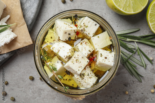 Fototapeta Flat lay composition with pickled feta cheese in jar on grey table obraz