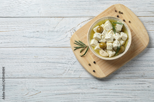 Fototapeta Flat lay composition with pickled feta cheese in bowl on white wooden table, space for text obraz