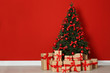 canvas print picture - Decorated Christmas tree and gift boxes near red wall. Space for text