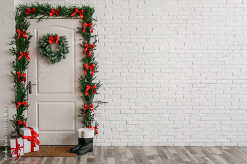 Fototapeta Stylish hallway interior with decorated door and Christmas gifts, space for text obraz