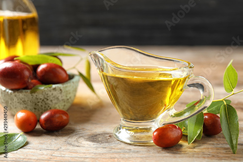 Glass sauce boat with jojoba oil and seeds on wooden table