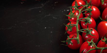 Overhead View, Fresh Red Cherry Tomatoes With Green Vine Leaves On Dark Marble Like Board, Wide Banner, Space For Text At Left Side