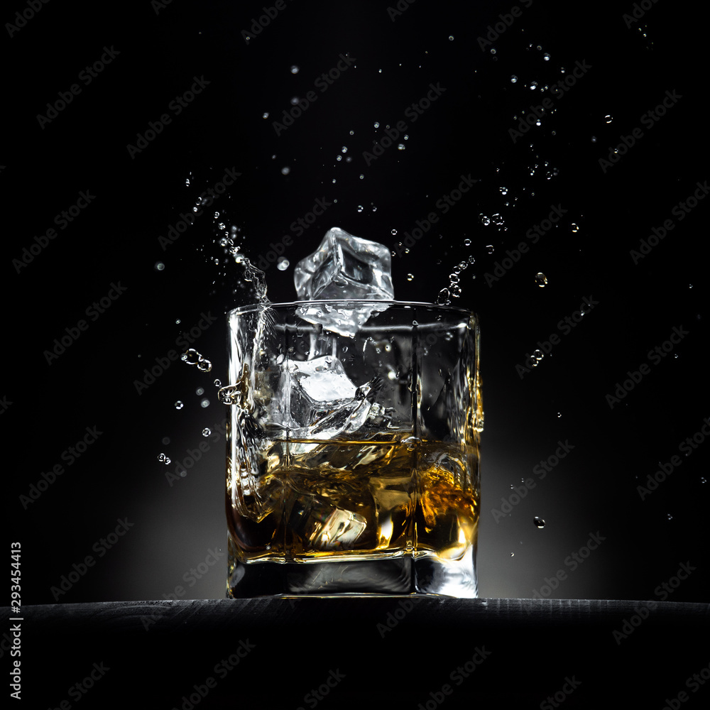 Fototapeta Glass of whiskey with ice cubes falling in it with splashes and drops. On the wooden table with dark background