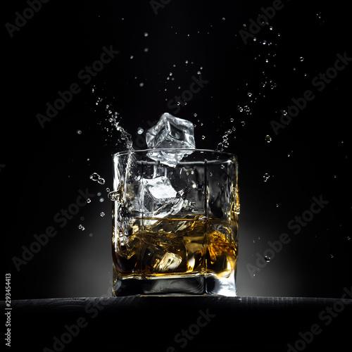 Szklanka whisky z kostkami lodu spadającymi w niej z rozpryskami i kroplami. Na drewnianym stole z ciemnym tłem