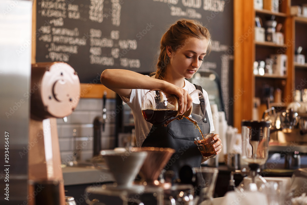 Fototapeta Professional barista preparing coffee using chemex pour over coffee maker and drip kettle. Young woman making coffee. Alternative ways of brewing coffee. Coffee shop concept.