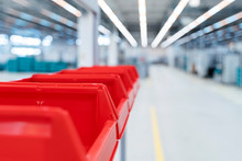 Row Of Red Plastic Containers In Factory Warehouse, Stuttgart, Germany