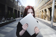 Businesswoman Covering Face With Laptop