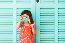 Little Girl Playing With Wooden Toy Camera