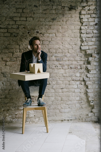 Businessman sitting on chair with architectural model - 293464242