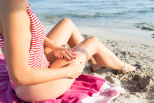 Woman Sitting On The Beach, Putting On Suncream