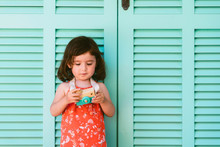 Portrait Of Little Girl With Wooden Toy Camera