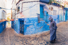 Man Walking In The Old City Of Chefchaouen With The Famous Blue Buildings, Chefchaouen, Morocco
