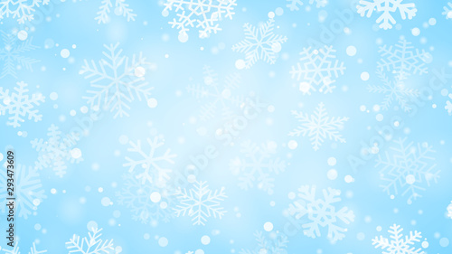 Christmas background of snowflakes of different shapes, sizes and transparency in light blue colors