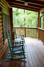 Two Rocking Chairs And A Swing On A Wooden Wrap Around Deck