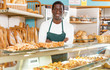 Confident baker in apron behind counter