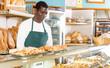 Baker working behind counter in bakeshop