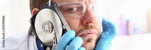 Repairman attached the hard drive of the computer to his ear Fotobehang