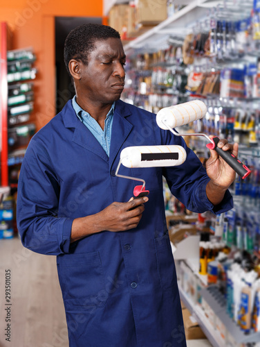 Fototapety, obrazy: salesman arranging different goods on stand in shop