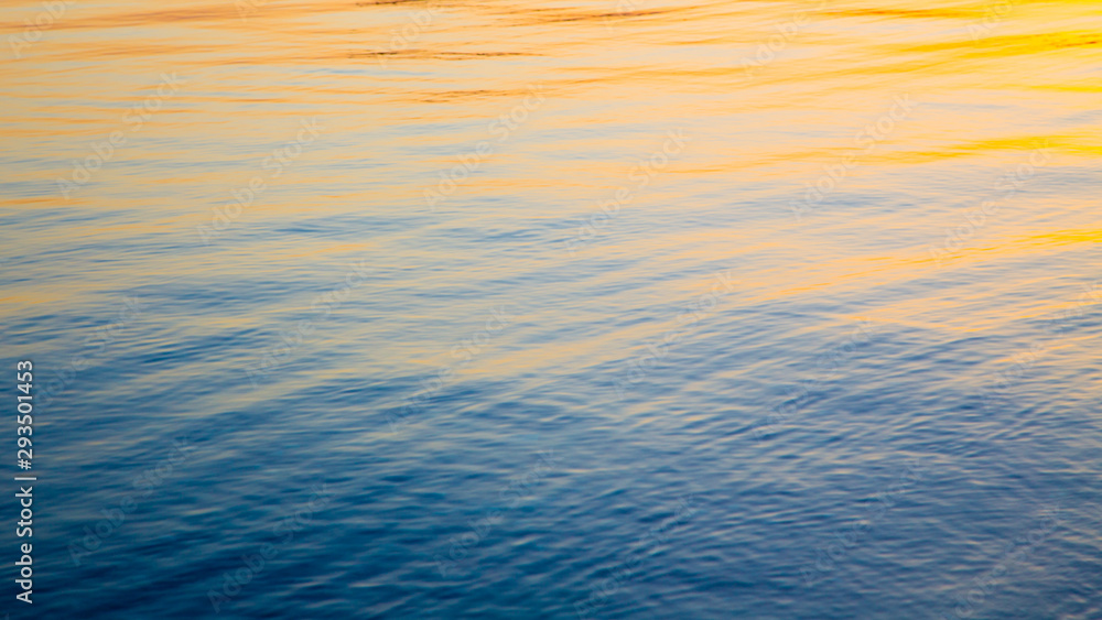 Fototapety, obrazy: Clear water texture in blue and orange. Background of the ocean and the sea backlit by the sun. Soft waves. Natural water