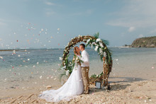 Wedding Ceremony On A Tropical Beach In Blue. Happy Groom And Bride Kissing  Under The Arch Decorated With Flowers On The Sandy Beach. Rose Petals Fall From Above. Wedding And Honeymoon Concept.