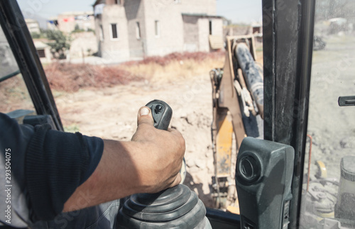 Male hand holding a control joystick. Work in excavator