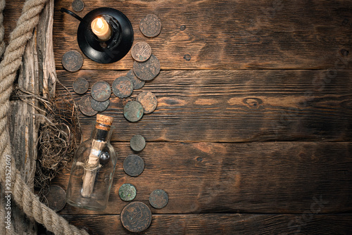 Fényképezés  Pirate letter parchment in a glass bottle on brown wooden table background