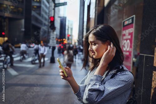 brunette girl using her cellphone to reach a friend outside Canvas Print