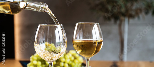Fototapeta Waiter pouring white wine into wineglass.  obraz