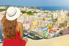 Holidays In Italy. Back View Of Beautiful Girl With Hat On Wall Looking At Stunning Sight Of Procida Island, Italian Capital Of Culture 2022.