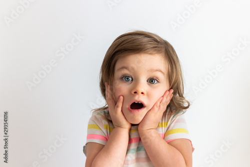 Surprised shocked toddler child with her hands on cheeks and blue eyes wide open Wallpaper Mural