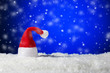 canvas print picture - Santa Claus hat on blue snowing background with copy space