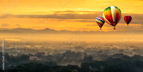 Poster Balloon Landscape with hot air balloons flying low over mountain with misty and sunrise background.