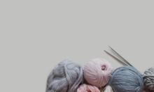 Woolen Yarn And Knitting Needles On Grey Backdrop