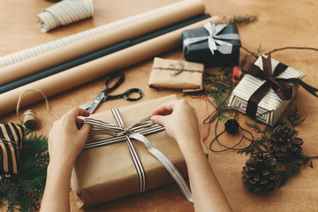 Hands wrapping stylish christmas gift box in craft paper and scissors, rustic  presents, thread, pine branches and cones on wooden table. Wrapping christmas gifts