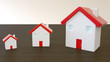 Three miniature houses with red roof on wooden, with blurred background. Image for property real estate, mortgage, insurance and home loan concept.