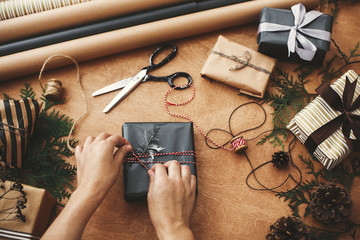 Wrapping christmas gifts flat lay. Hands wrapping stylish christmas gift box in black paper and scissors, rustic presents, thread, pine branches and cones on wooden table
