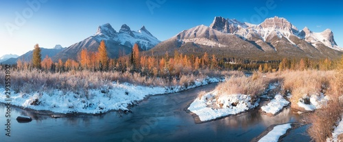 Foto auf AluDibond Cappuccino Panorama of autumn sunrise at The Three Sisters mountain with colorful trees Canmore, Alberta with reflection in calm water of Policeman creek surrounded by trees and bushes. First snow in mountains