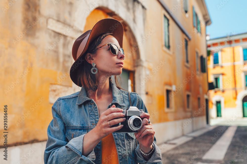 Fototapeta Attractive tourist with a retro camera
