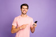 Leinwanddruck Bild - Portrait of his he nice attractive cheerful cheery glad content guy wearing pink tshirt holding in hands recommending digital device isolated on violet purple lilac pastel color background