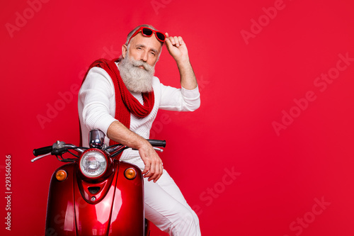 obraz lub plakat Portrait of classy elderly person touching his eyeglasses eyewear sit on bike wearing white jumper trousers pants isolated over red background
