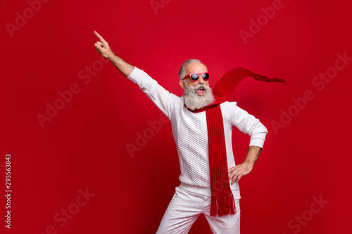 Cool santa character aged man directing finger on advert banner wear sun specs knitted clothes isolated red background - 293563843