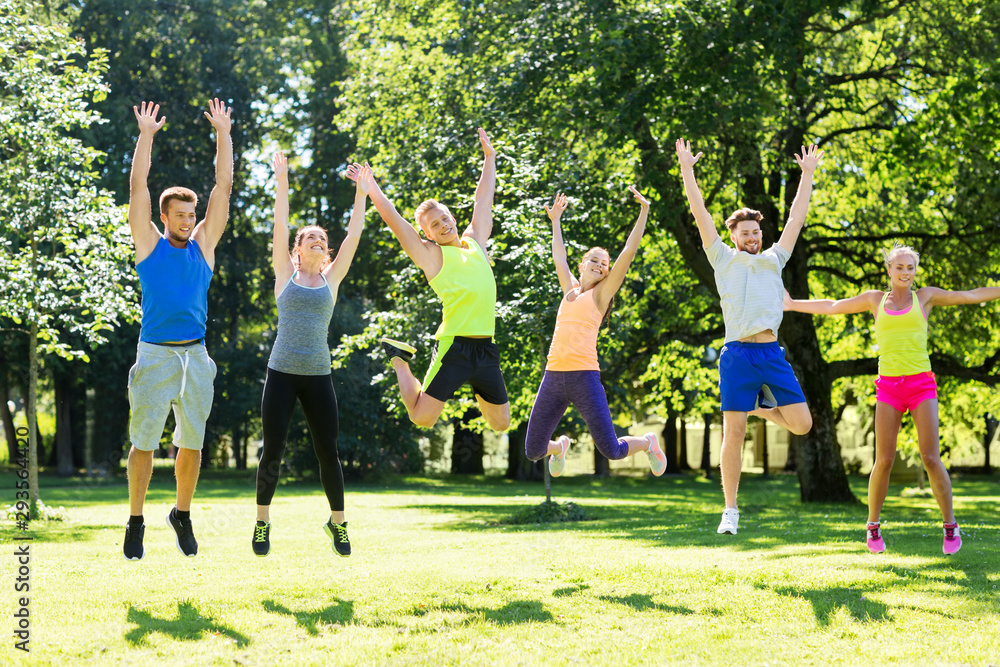 Fototapeta fitness, sport and healthy lifestyle concept - group of happy people jumping high at park in summer