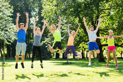 obraz lub plakat fitness, sport and healthy lifestyle concept - group of happy people jumping high at park in summer