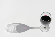 Glass Of Red Wine On A White Background With Dark Deep Shadow.