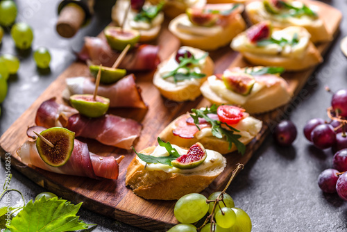Fototapeta Assorted brushetta - italian apetizer or traditional spanish tapas for sharing. Party food on catering platter. Antipasti with meat, cheese and fruits. obraz