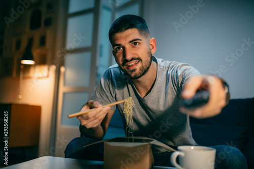 man eating chinese noodles and watching television at his home. night scene