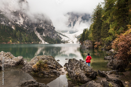 Foto  Women with red rain jacket enjoying the peaceful mystic view of a mountain lake with cloudy dramatic mountains in the background on a rainy autumn day